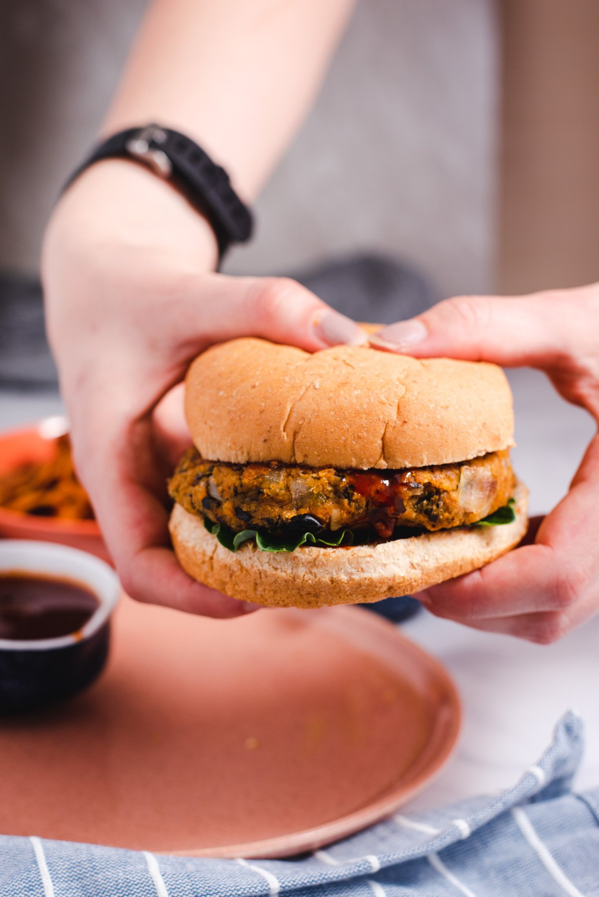 Two hands holding a sweet potato burger