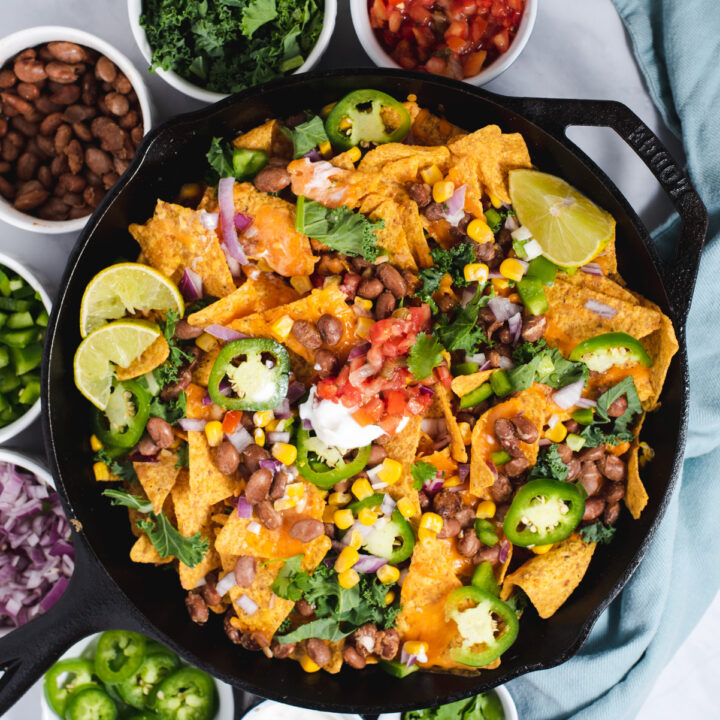 Cast iron skillet filled with nachos surrounded by bowls of nacho ingredients