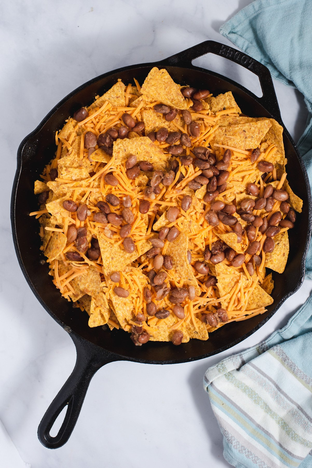 Tortilla chips with shredded cheese and pinto beans in cast iron pan