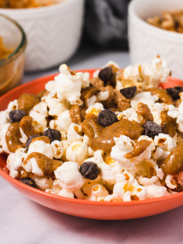 Orange bowl filled with popcorn, walnut butter and chocolate chips