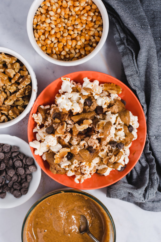Orange popcorn filled bowl next to bowls filled with chocolate chips, popcorn kernels and walnuts