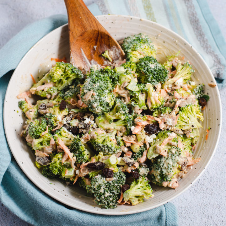 Broccoli salad in a white bowl on a blue cltoh with a wooden serving spoon