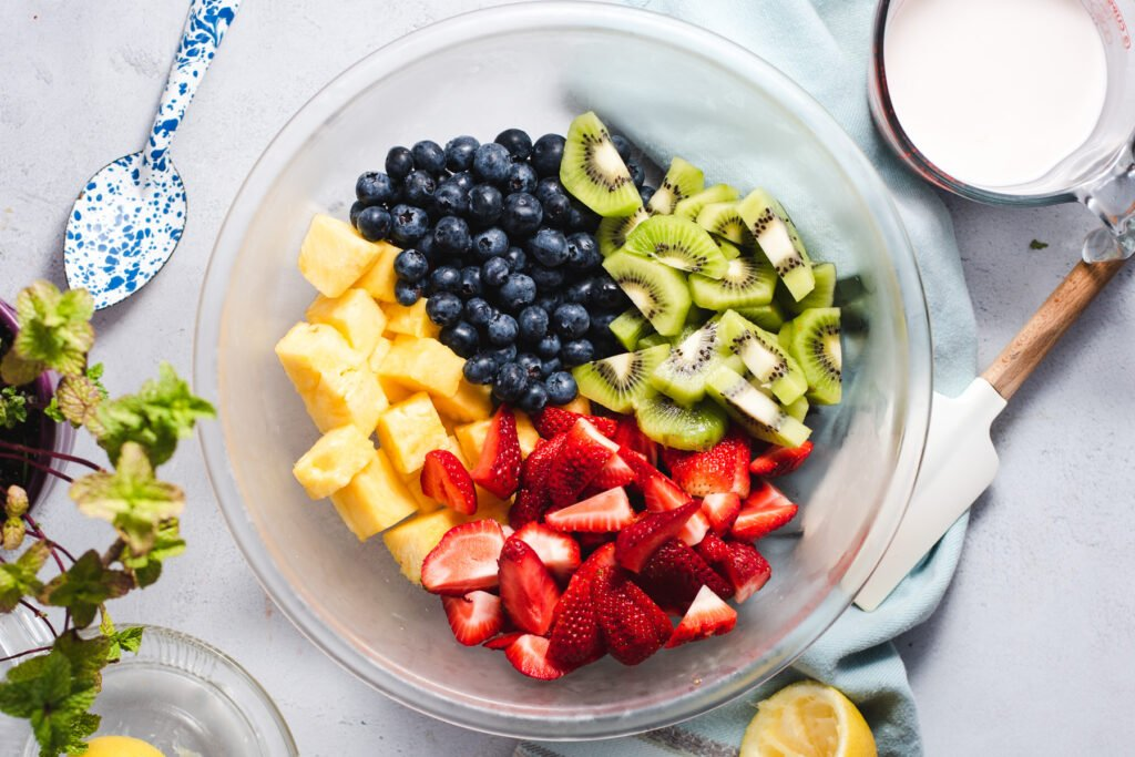 Strawberries, pineapple, blueberries and kiwi in a glass bowl