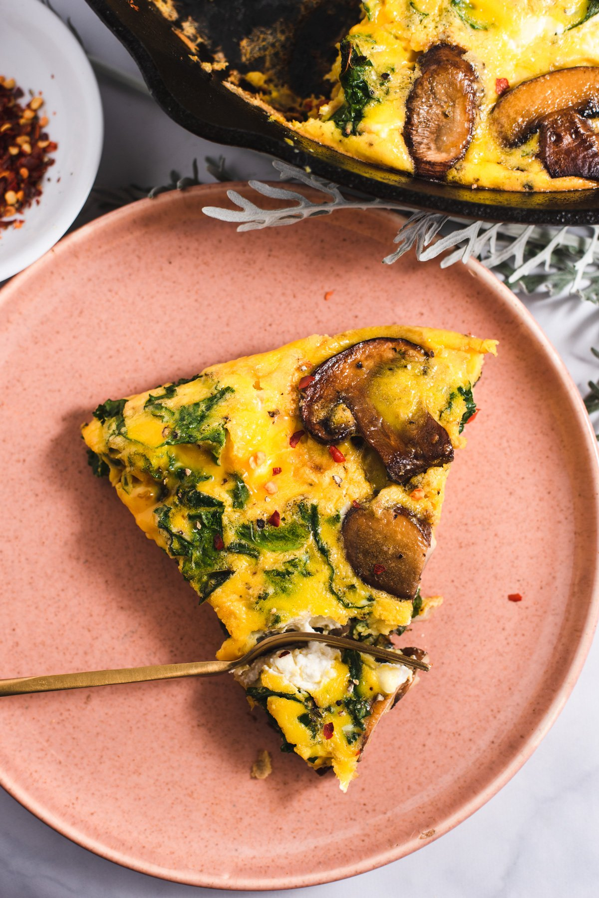 Slice of frittata on a pink plate with a gold fork