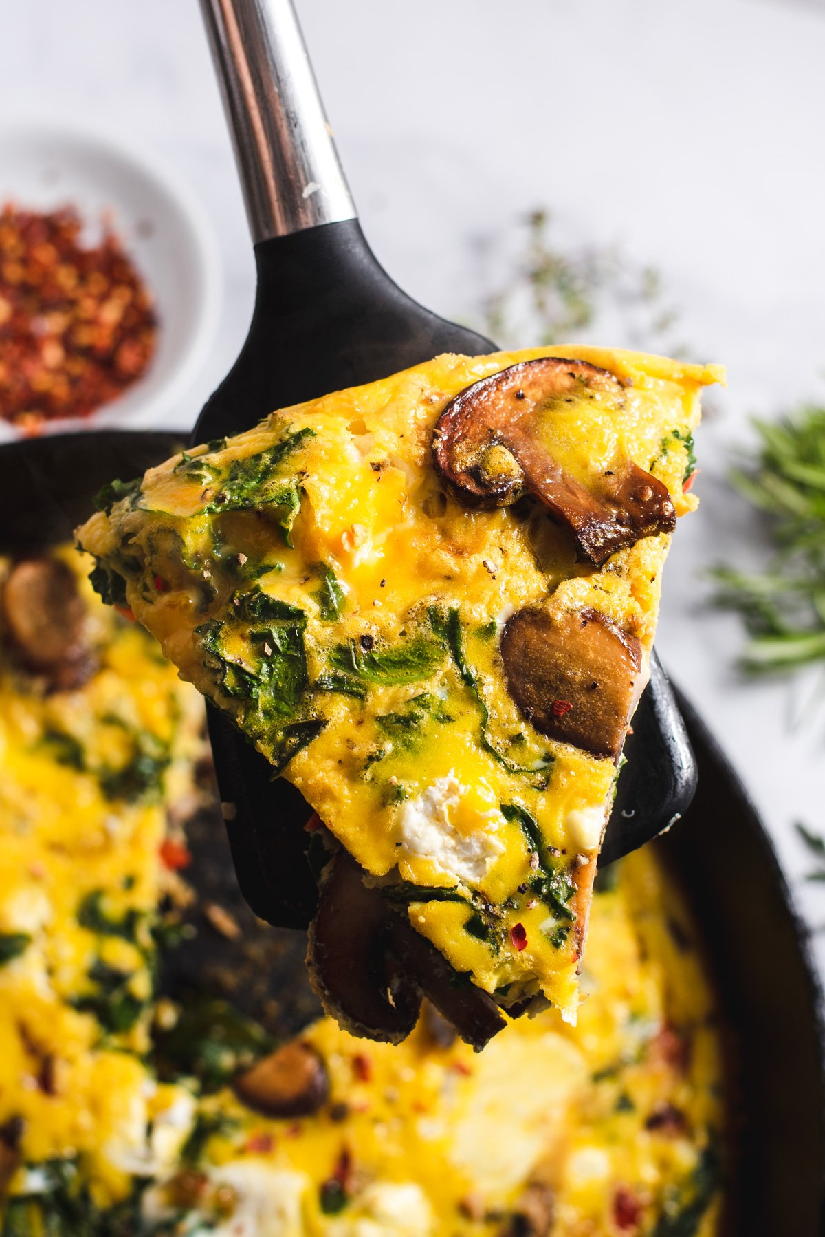 Pie shaped slice of frittata on a spatula