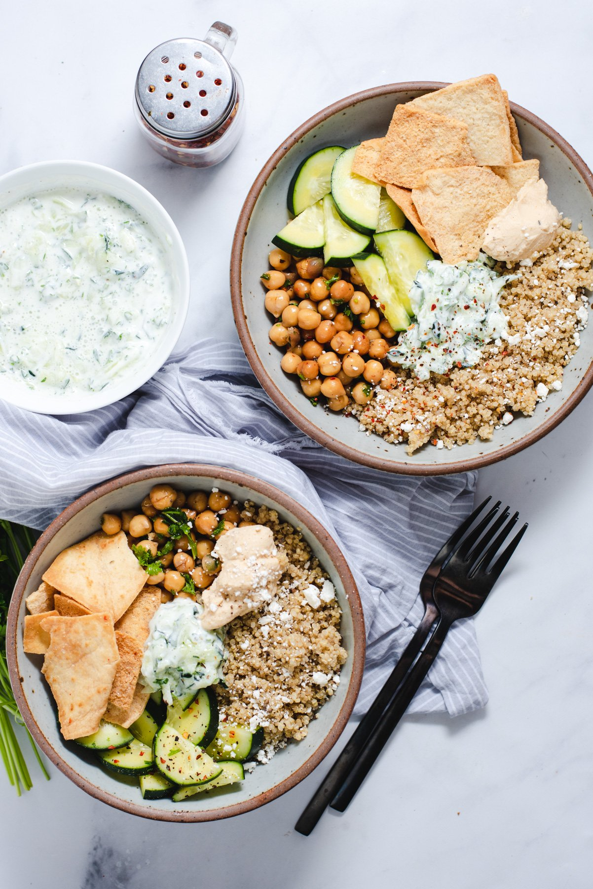 Two bowls filled with quinoa chickpea bowl ingredients