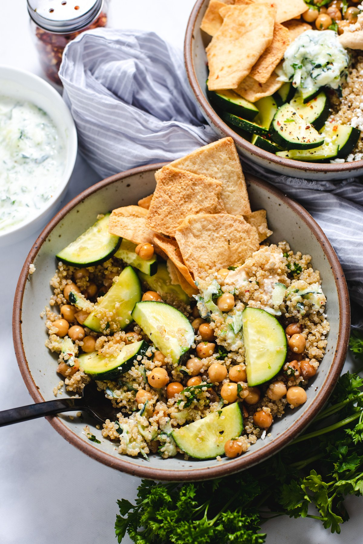 Gray ceramic bowl filled with cucumbers, quinoa, chickpeas and pita chips
