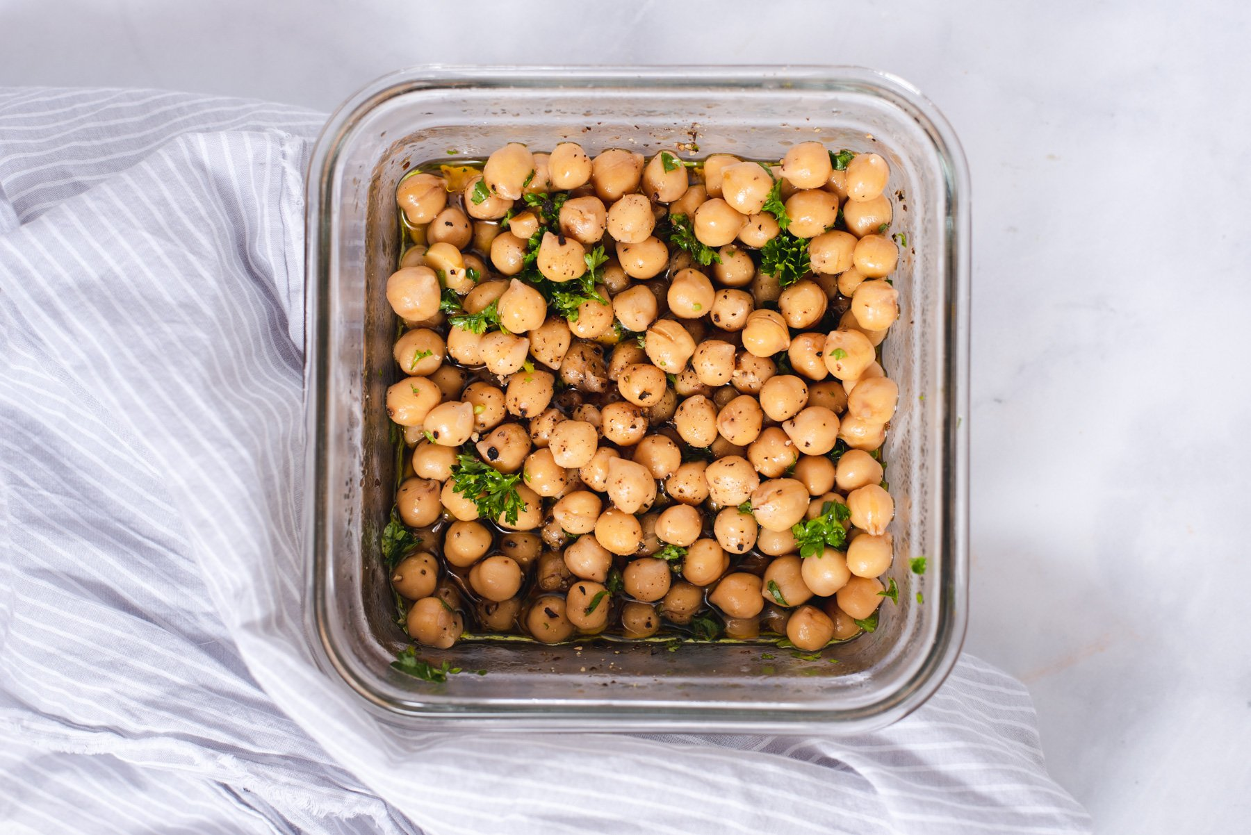 Square glass container filled with chickpeas and parsley