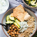 Gray speckled ceramic bowl showing separated quinoa, chickpeas, pita chips, cucumber and tzatziki sauce