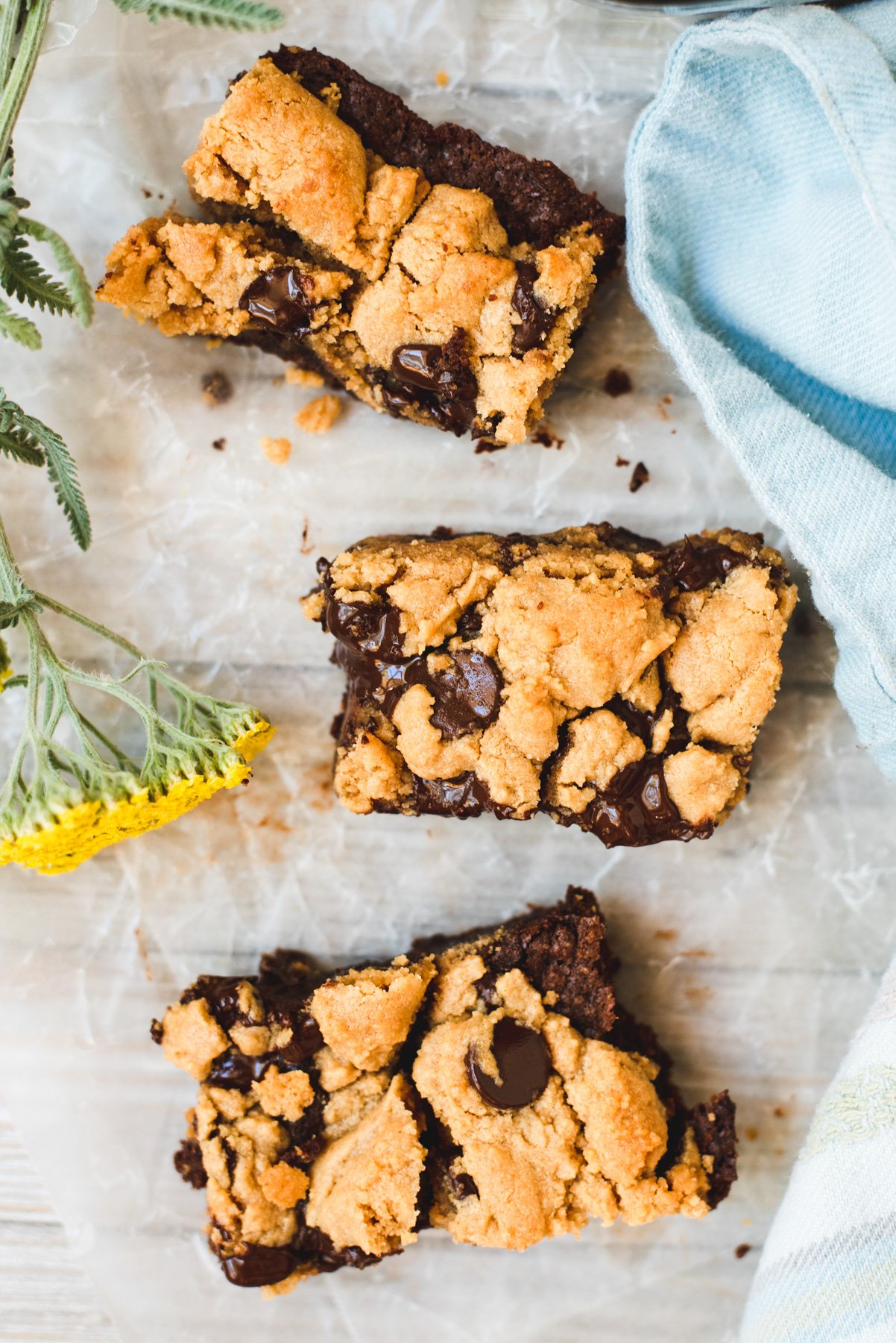 Three slices of peanut butter brookies on a white background next to a yellow flower