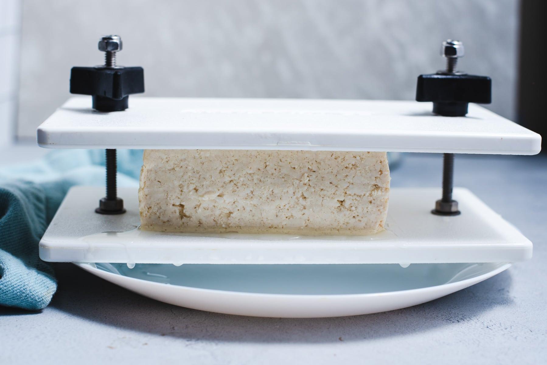 Tofu being pressed in white tofu press