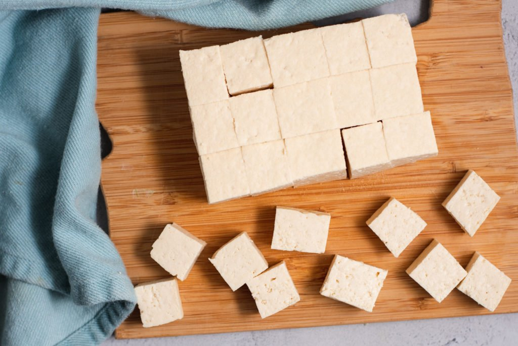 Cubed tofu on wooden cutting board
