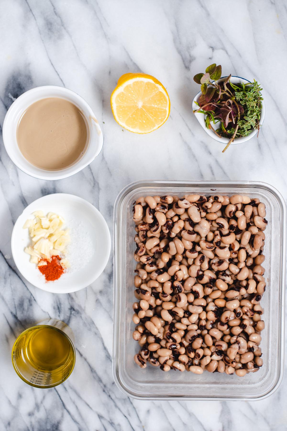 Ingredients to make black eyed pea hummus on a marble background