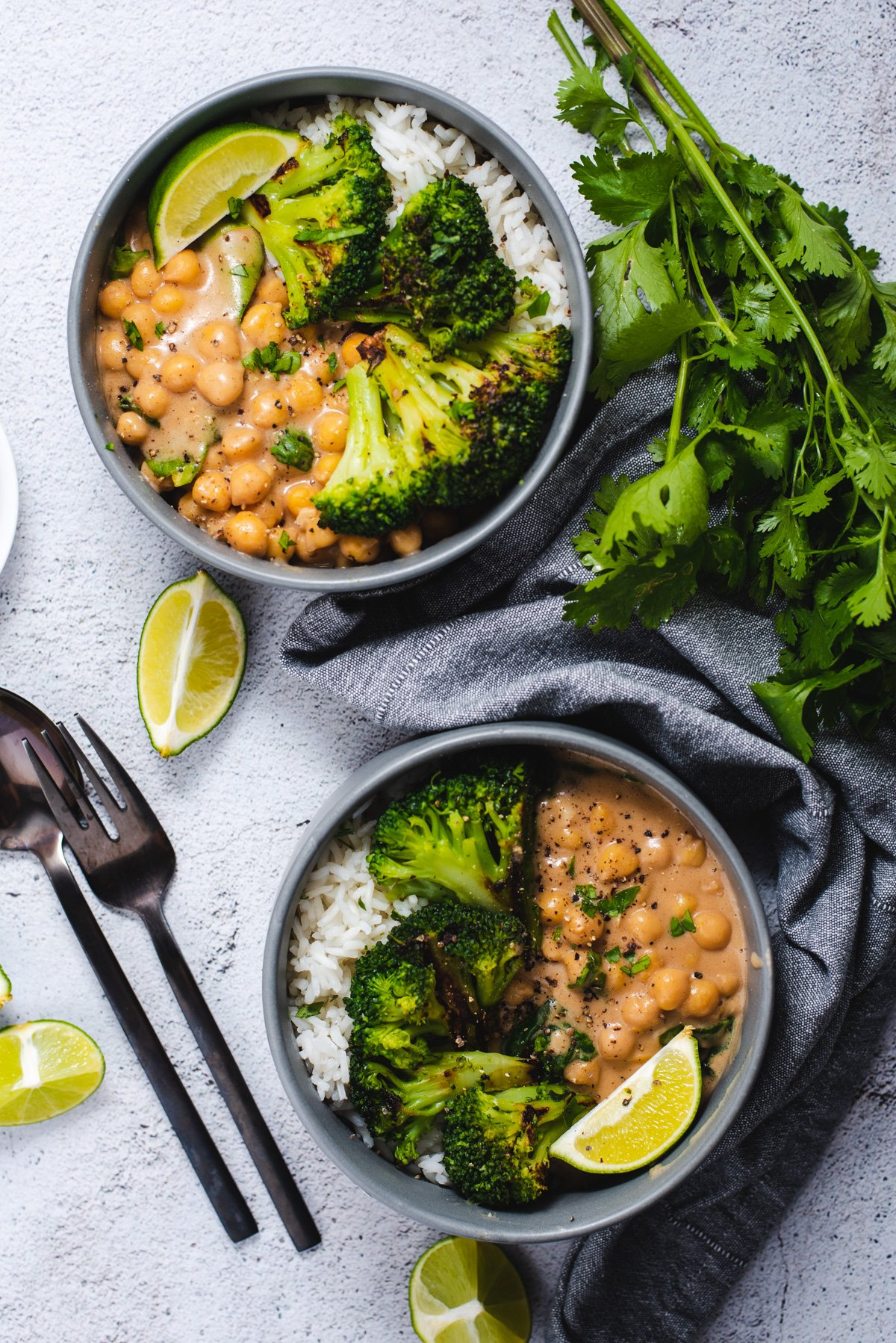Two gray bowls filled with chickpeas, broccoli and rice on a gray background