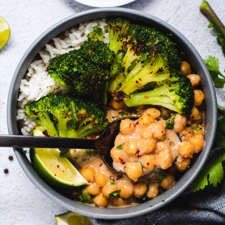 Gray bowl filled with chickpeas, broccoli, rice and a lime wedge