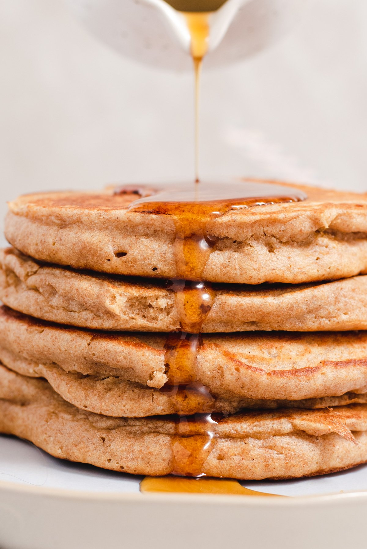 Close up of syrup dripping off a stack of whole wheat pancakes