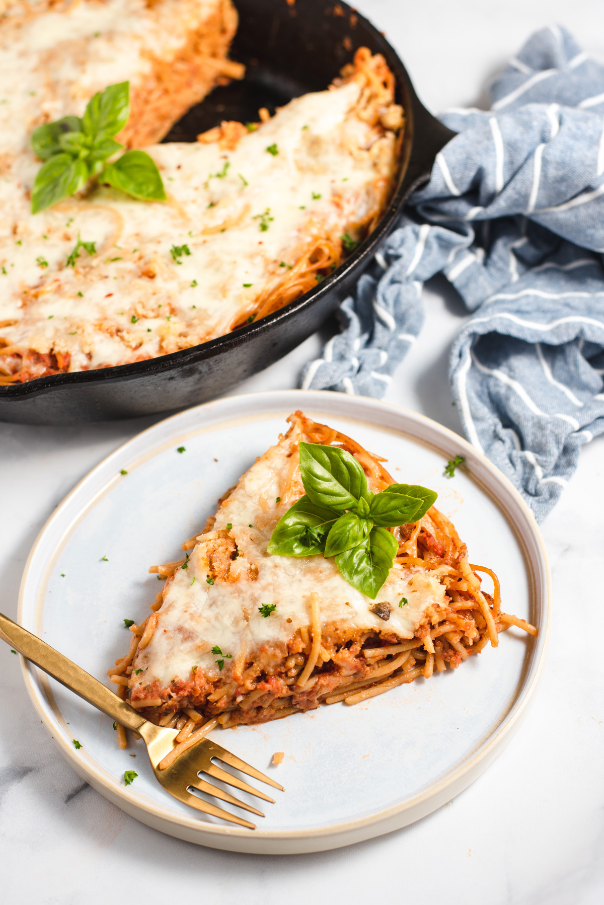 Slice of spaghetti pie on a plate with cast iron pan in the background