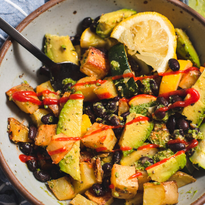 Gray bowl filled with roasted vegetables and black beansa