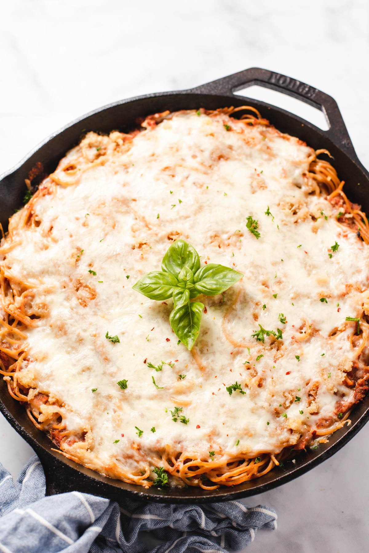 Cast iron pan with cheese topped spaghetti