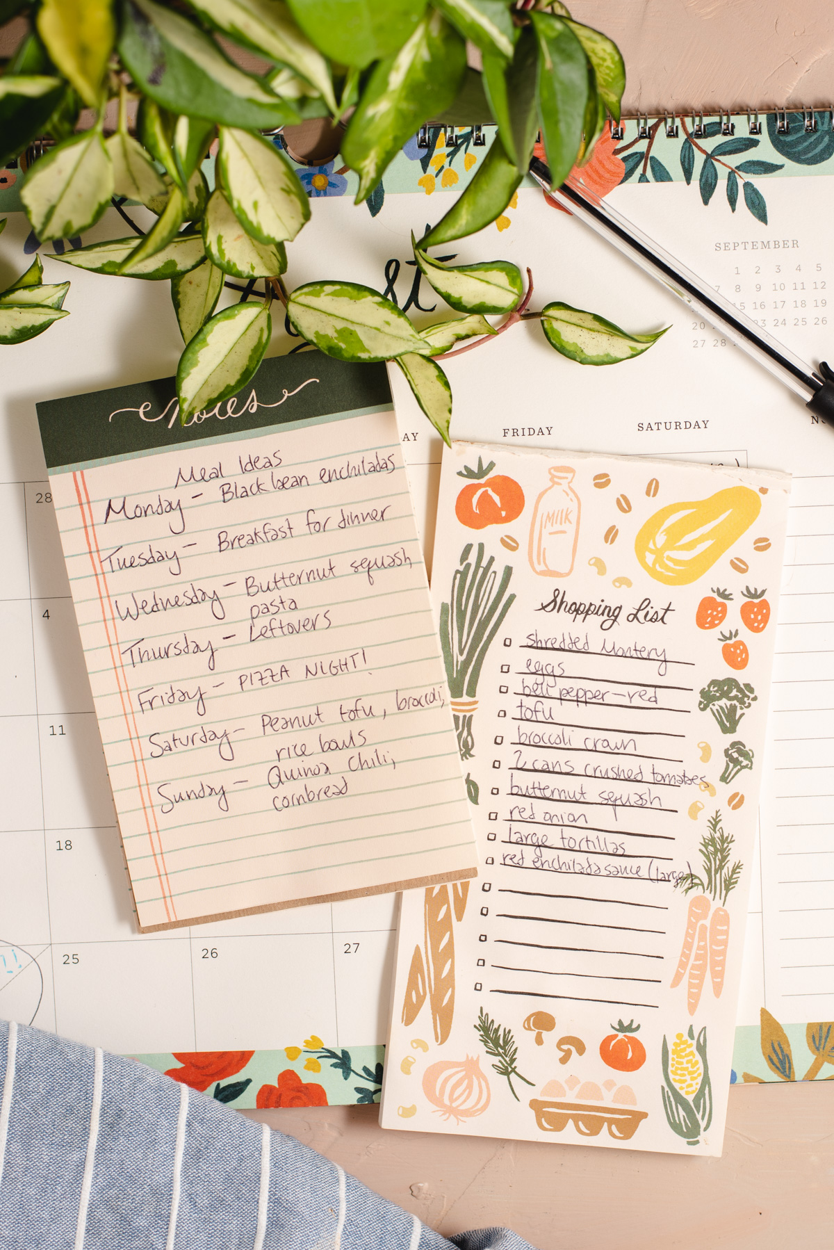 Shopping list and meal plan list sitting next to a plant vine