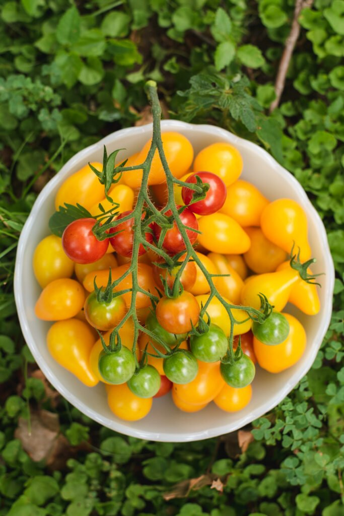 Yellow grape tomatoes and cherry tomatoes in white bowl