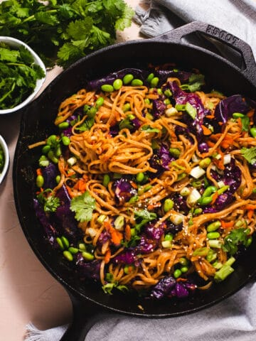 Black cast iron pan filled with almond butter stir fry