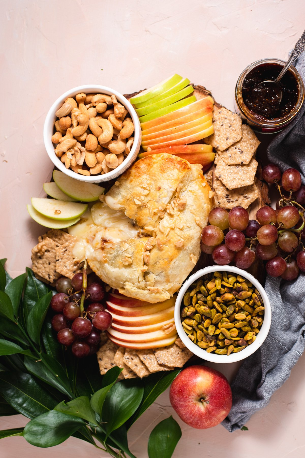 Overhead view of baked brie board with grapes, crackers, nuts and sliced apples