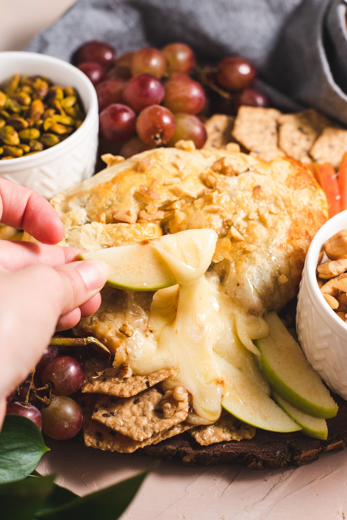 Hand dipping green apple in melted brie surrounded by nuts and fruit