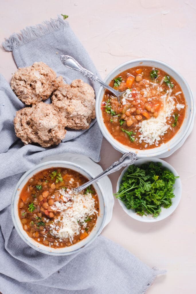 Two bowls of lentil soup next to drop biscuits and fresh parsley