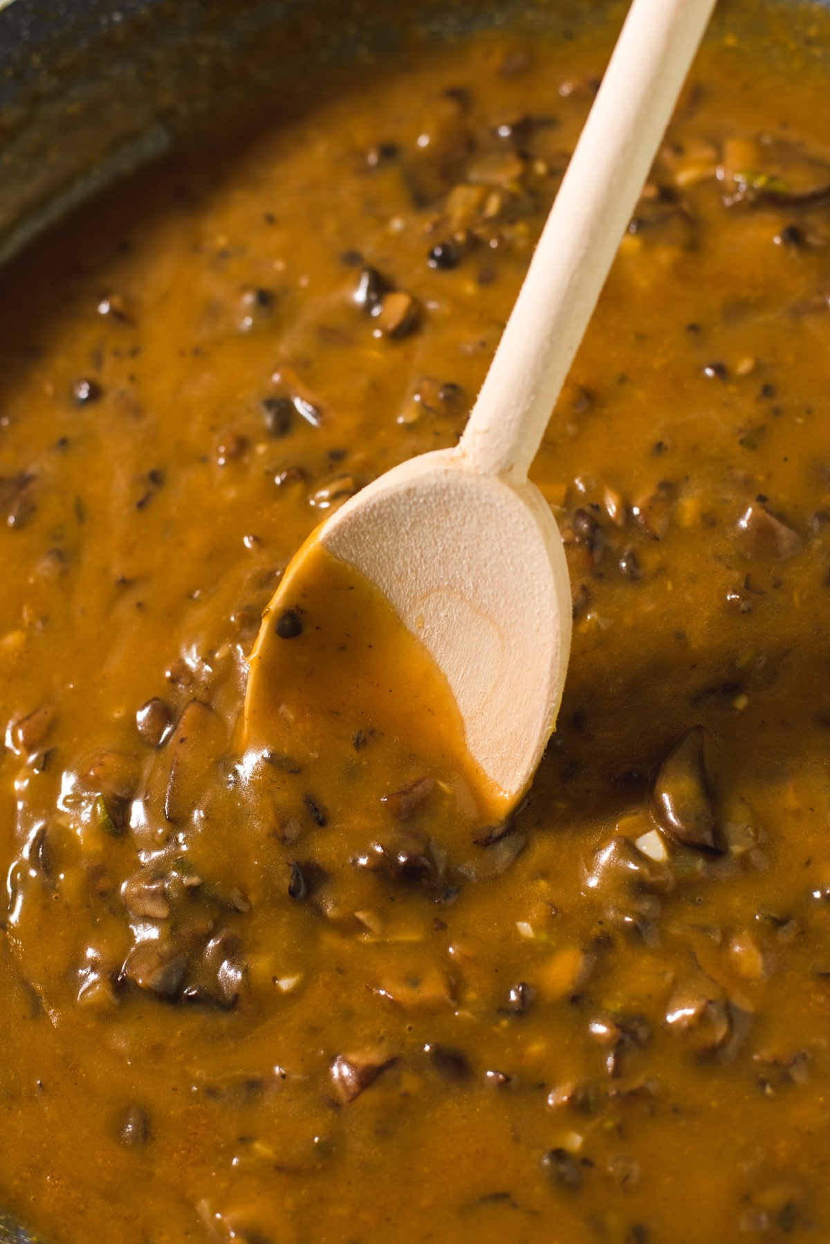 Close up of wooden spoon coated in gravy