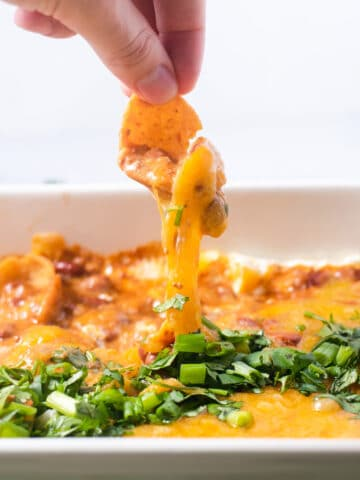 Frito pulling cheese from casserole dish