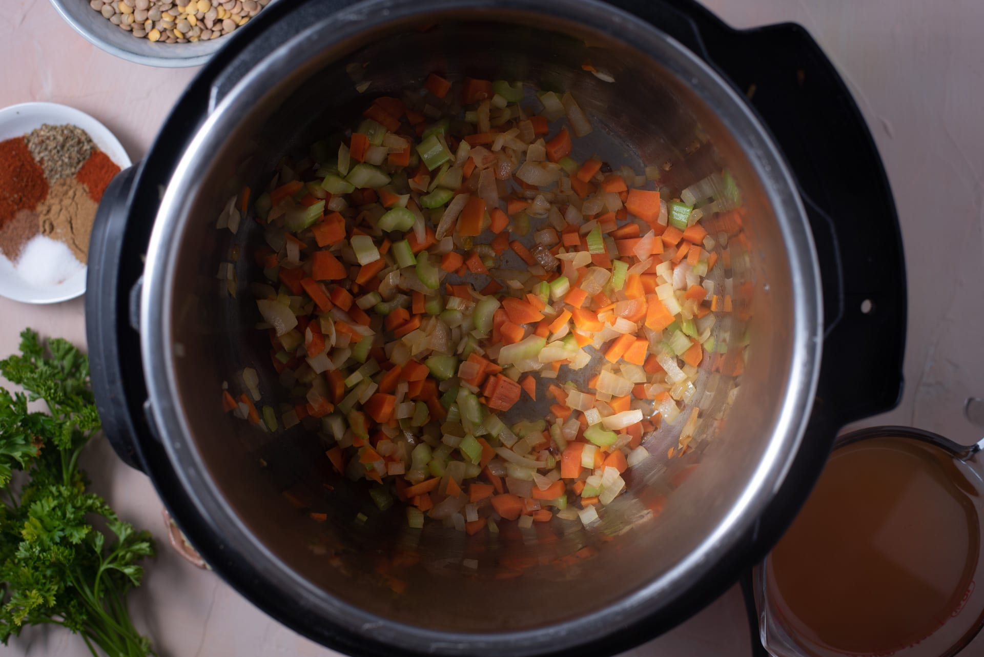 Overhead view of onion, carrot and celery in Instant Pot
