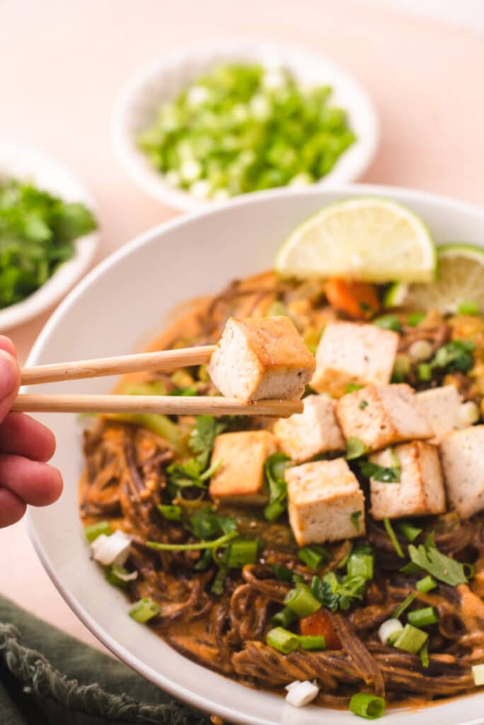 Chopsticks lifting piece of tofu out of bowl with noodles