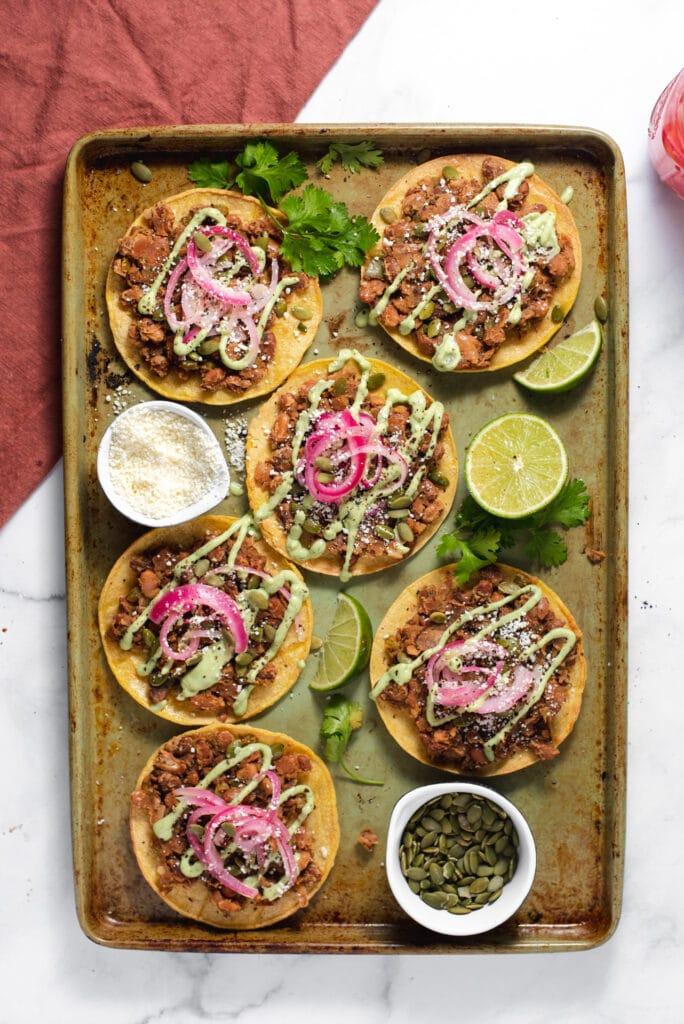 Six tostadas on a green sheet pan
