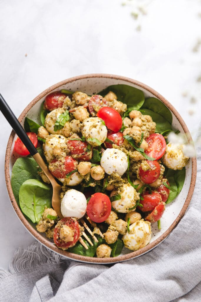 Bowl with spinach, mozzarella, chickpeas and tomatoes on spinach