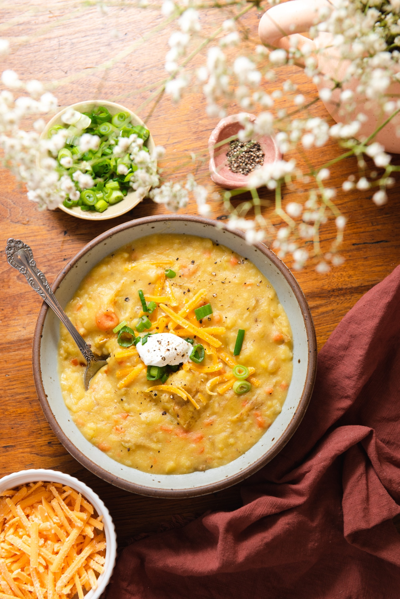 Potato soup in gray bowl surrounded by green onions and out of focus white flowers