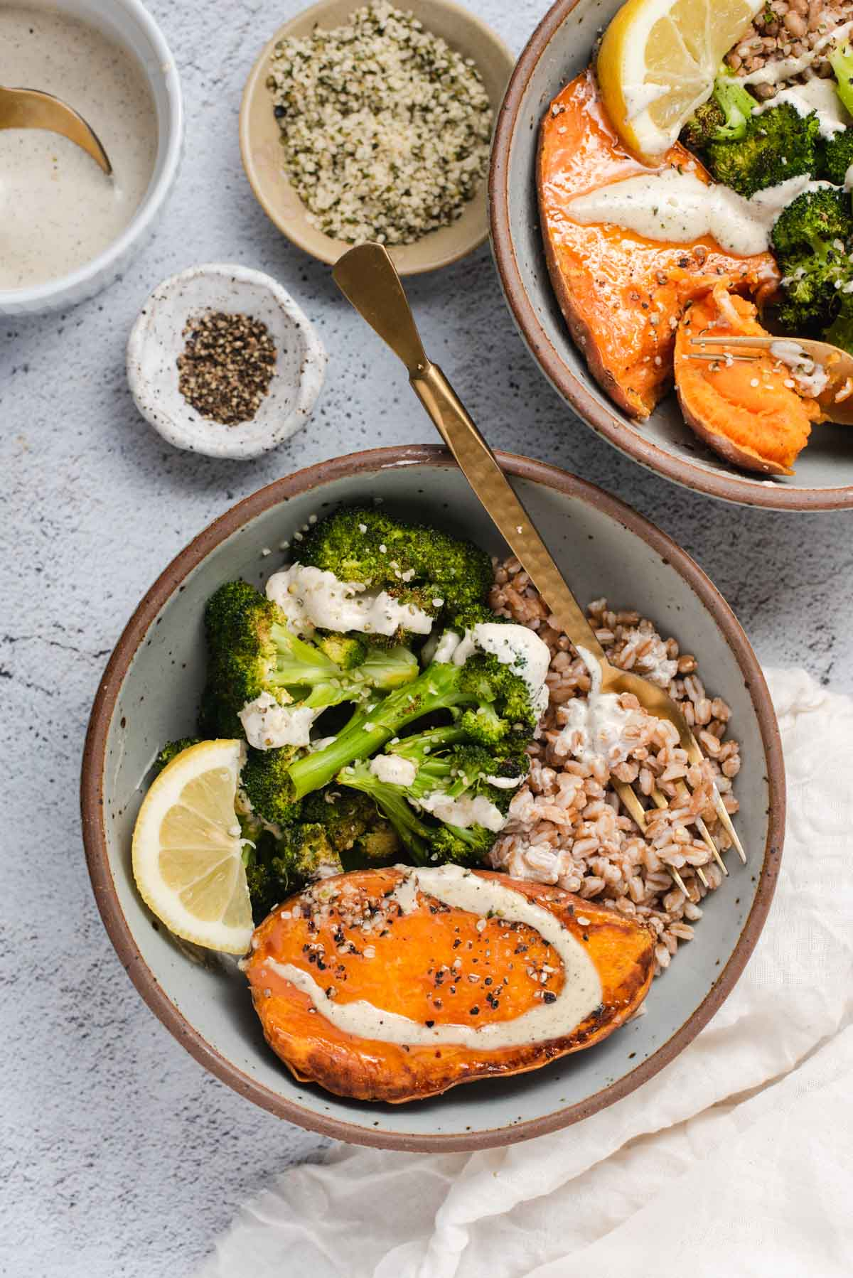 Overhead view of gray bowl filled with sweet potato half, farro and broccoli