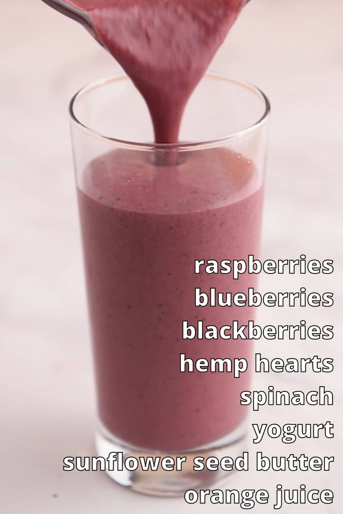 Red smoothie being poured into tall glass with ingredients list