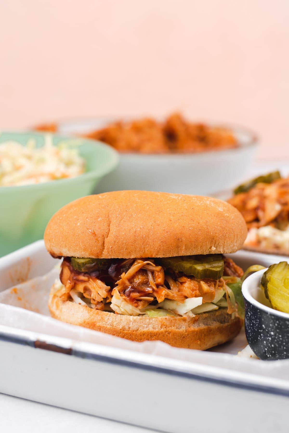 Side view of jackfruit sandwich on white tray with green and white bowl in the background