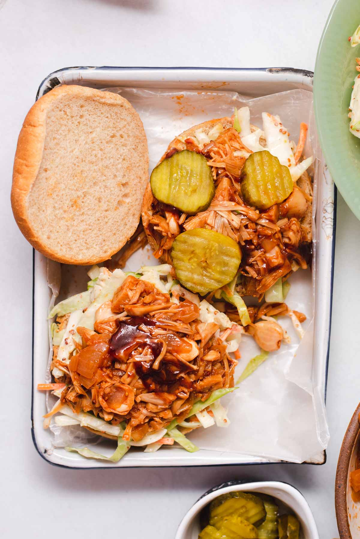 Two open faced sandwiches topped wiht coleslaw, jackfruit and pickles on a white tray