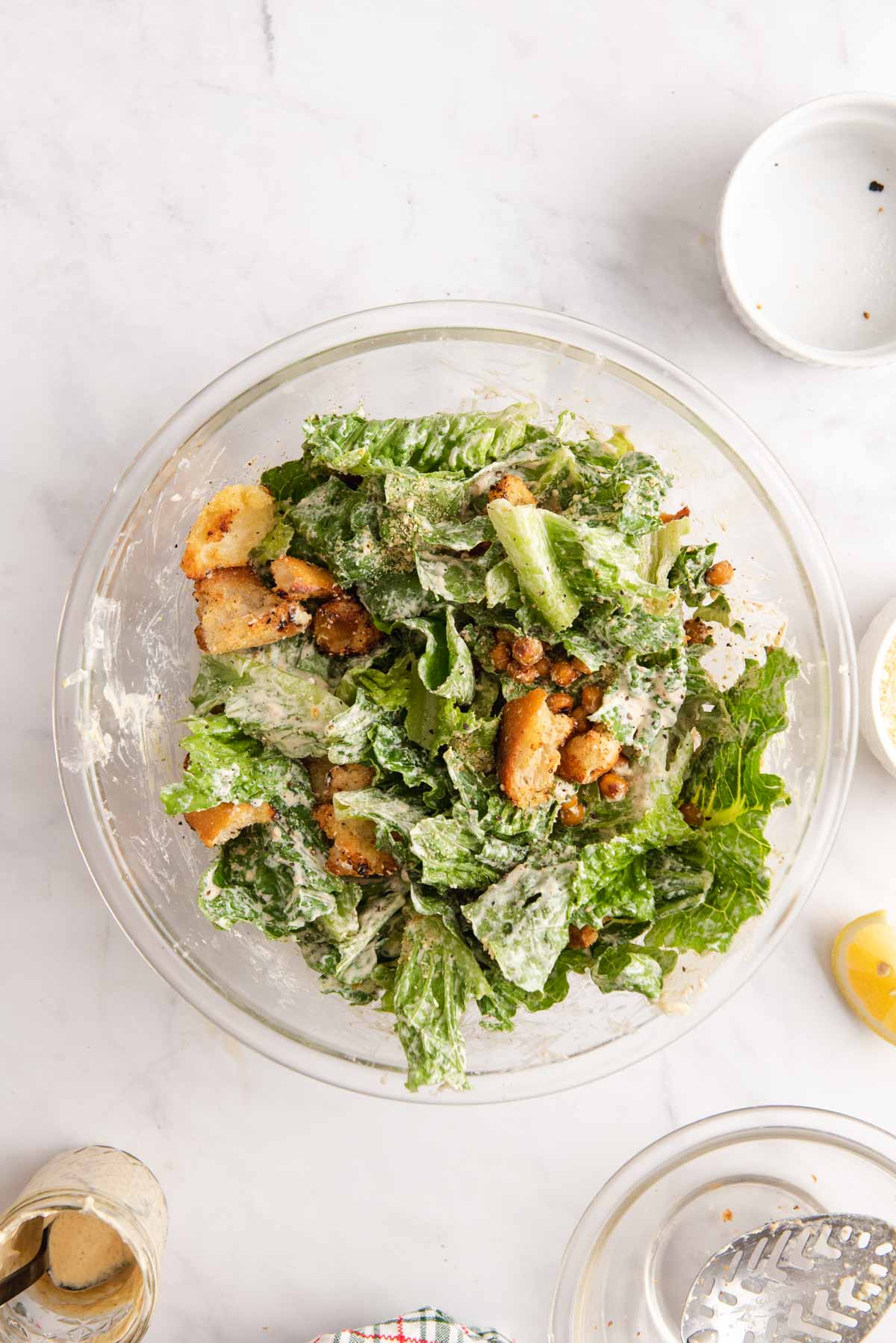 Overhead view of caesar salad in a large glass bowl on a marble background