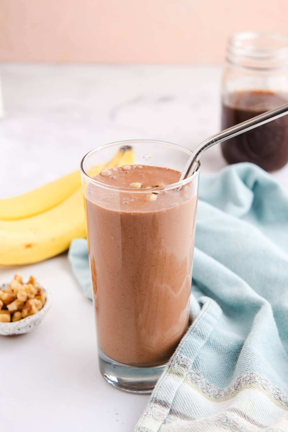 Tall glass of chocolate smoothie next to bananas, nuts, and blue cloth