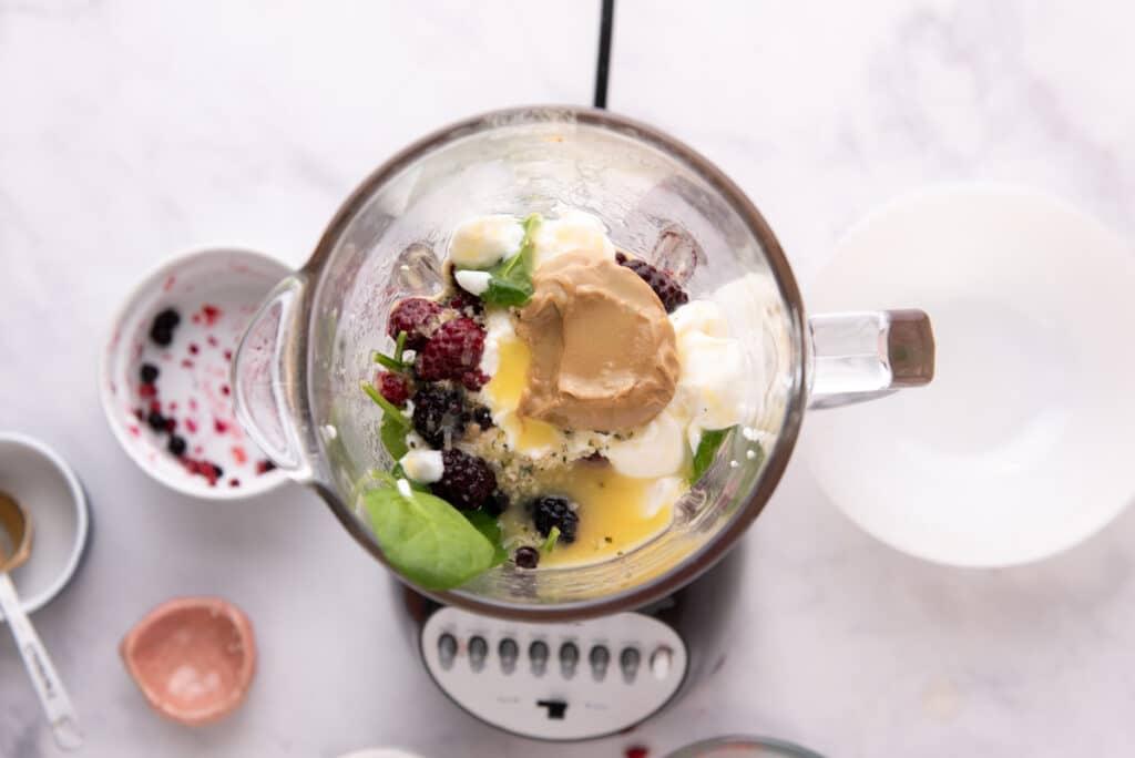 Overhead view of smoothie ingredients in blender before blending
