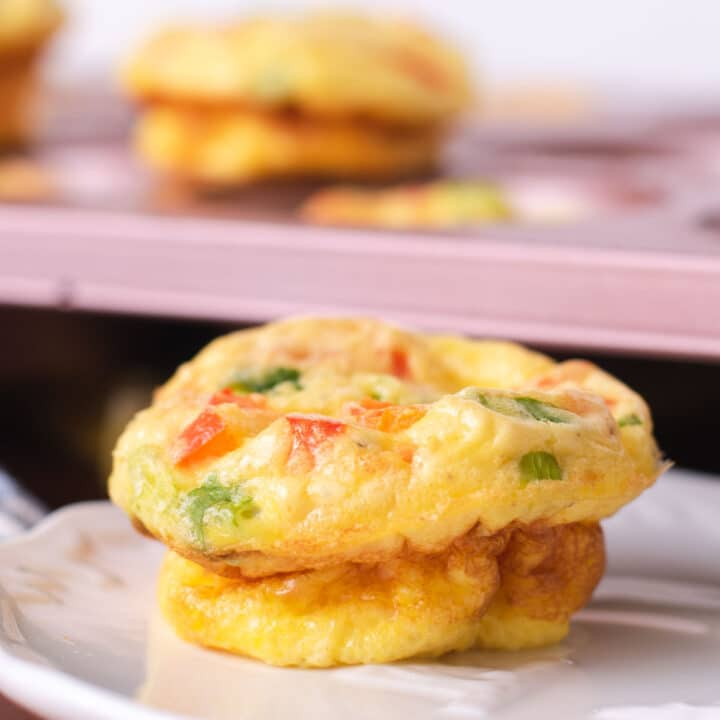 Single egg muffin on a white plate with more muffins in the background