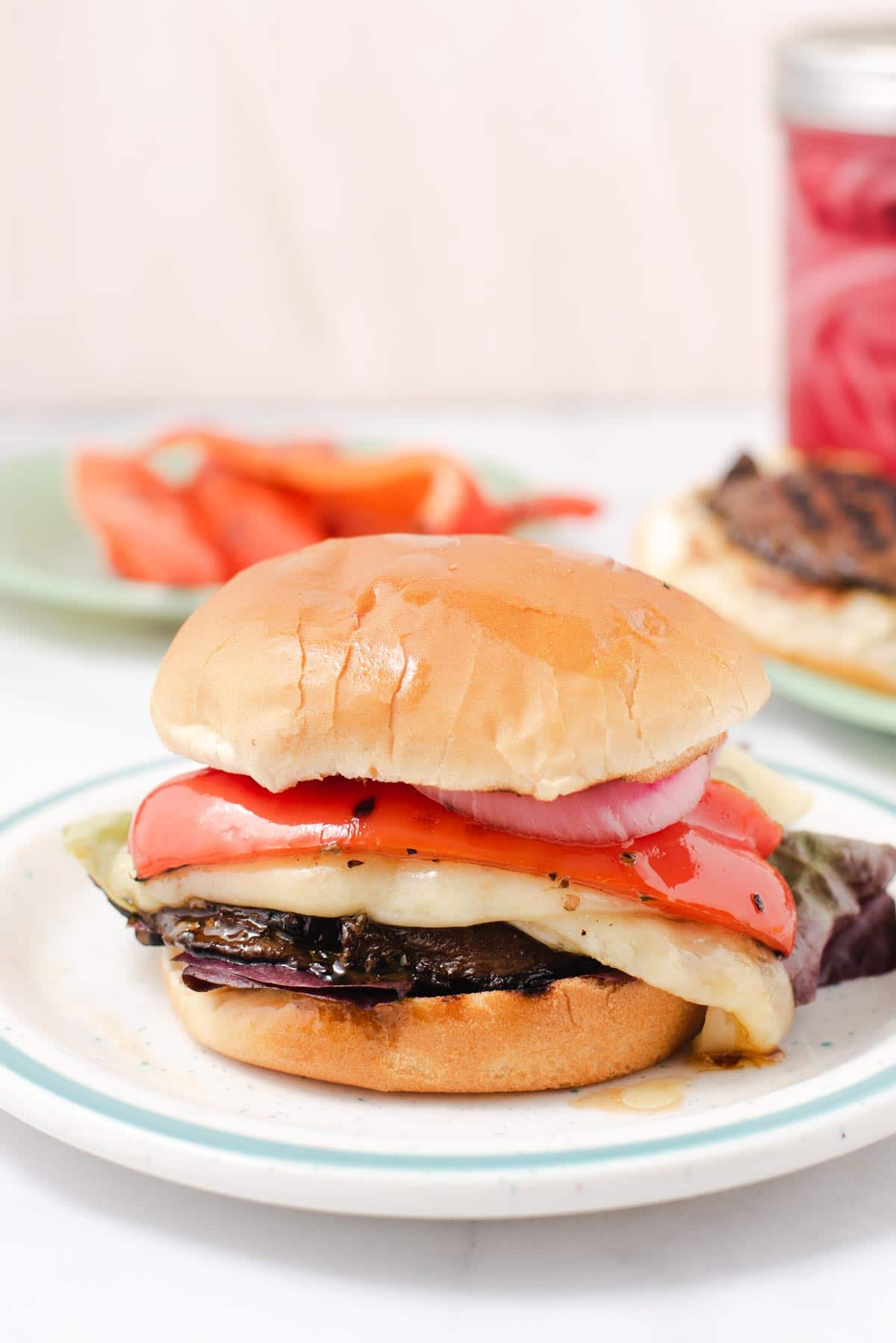 Mushroom burger topped with red bell pepper and melting cheese on a white plate