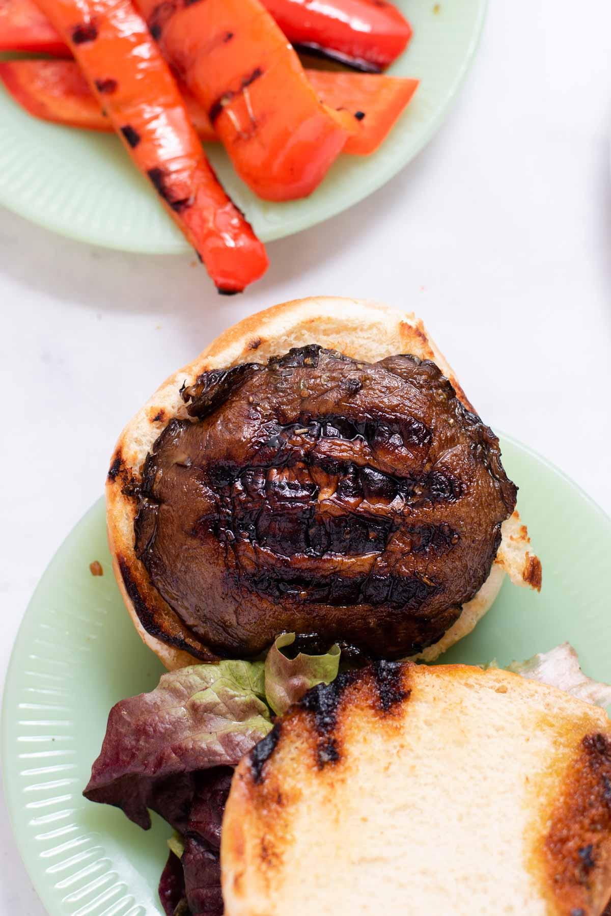 Overhead view of mushroom cap on a toasted bun on a jade plate
