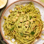 Overhead view of green spaghetti and chickpeas in a white bowl