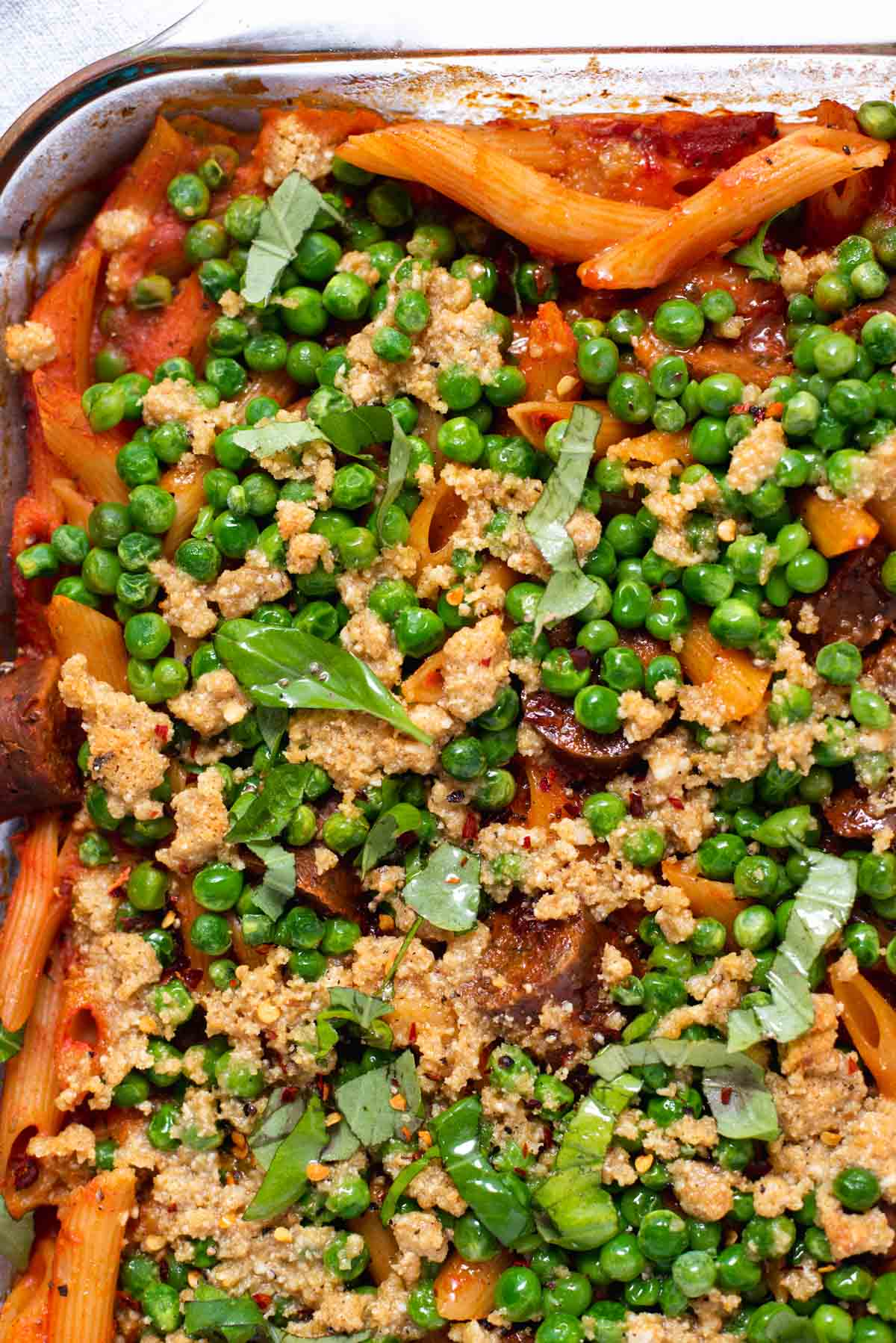 Close up of peas and breadcrumbs on pasta bake