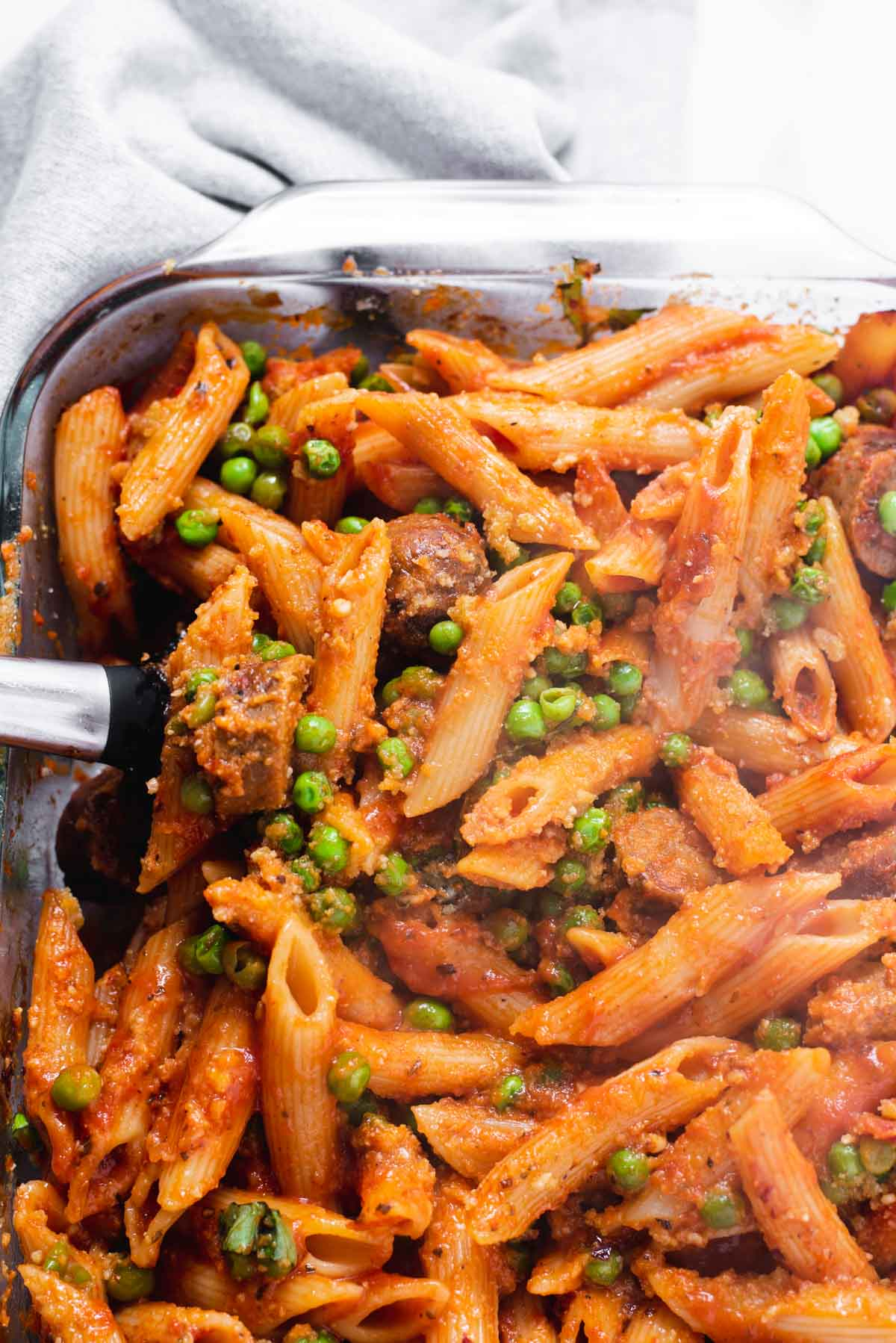 Close up of penne coated in marinara sauce with peas