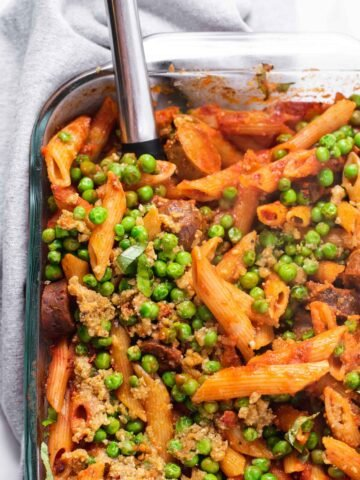 Overhead view of penne pasta with peas in a glass baking dish